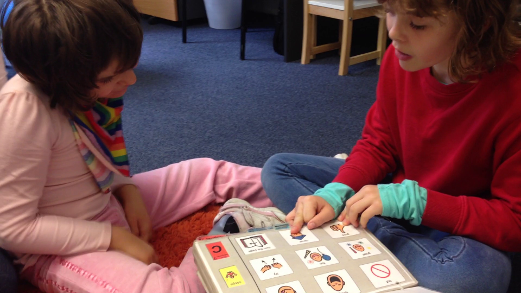 siblings interacting using a PODD communication book
